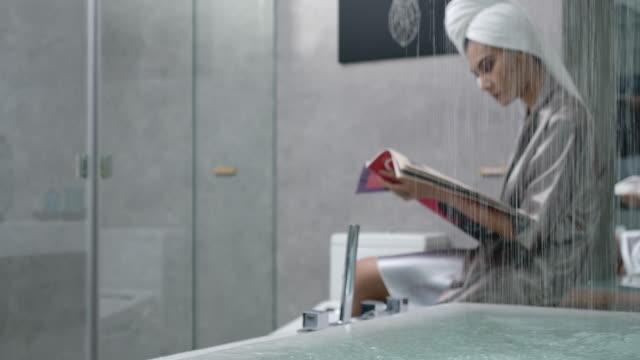 4k slow motion woman in shape wear silk pajamas sitting reading near the bathtub - bagno video stock e b–roll