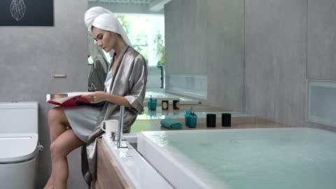 4k slow motion woman in shape wear silk pajamas sitting reading near the bathtub - bathroom stock videos & royalty-free footage
