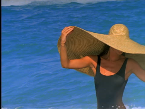 slow motion woman in swimsuit and straw hat walking on beach - straw hat stock videos & royalty-free footage