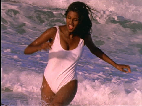 slow motion woman in swimsuit running in ocean toward camera - one piece swimsuit stock videos and b-roll footage