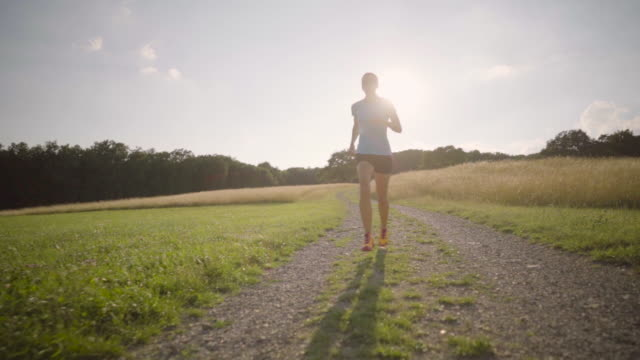 slow motion woman jogging in summer sunny back light outdoors