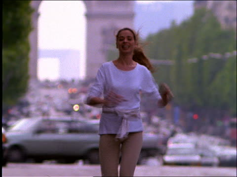 stockvideo's en b-roll-footage met slow motion woman jogging, jumping and raising arms on street / paris - jogster