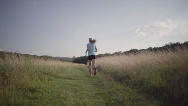 slow motion woman jogging on meadow betweeh high grass back view