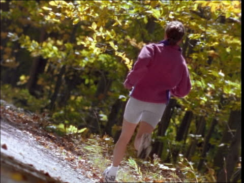 stockvideo's en b-roll-footage met canted slow motion woman jogging on tree-lined road away from camera in autumn - jogster
