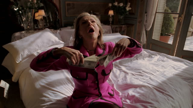 vídeos de stock e filmes b-roll de slow motion woman kissing handfuls of money on bed/ falling back and throwing bills in air/ bills floating - unidade monetária