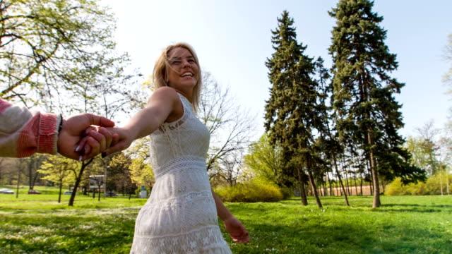 Slow motion: Woman leading her boyfriend through park
