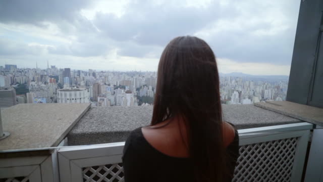 vídeos de stock, filmes e b-roll de slow motion: woman looking out over city in sao paulo, brazil - janela