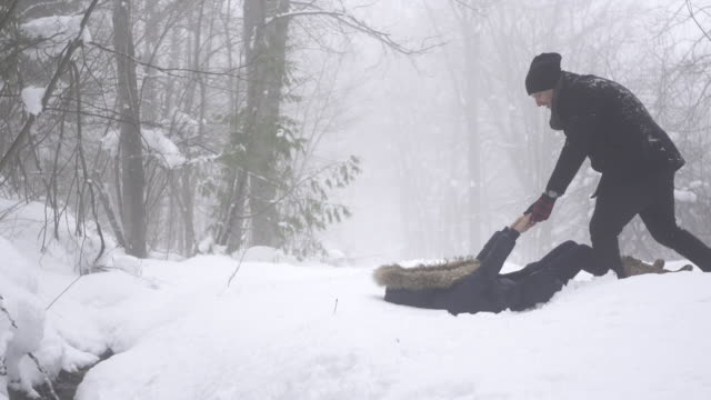 Slow motion woman pulls man down into snow 1