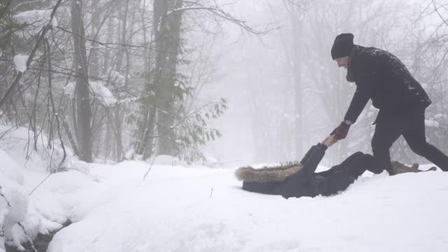 slow motion woman pulls man down into snow 1 - dra bildbanksvideor och videomaterial från bakom kulisserna