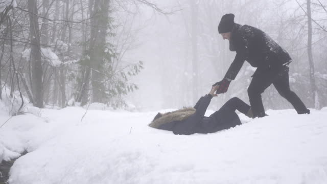 Slow motion woman pulls man down into snow 2