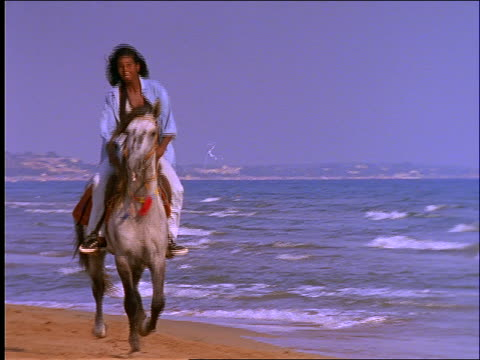 slow motion woman riding horse on beach - recreational horseback riding stock videos & royalty-free footage