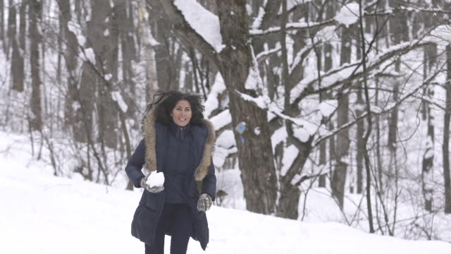 Slow motion woman running dodges snowball