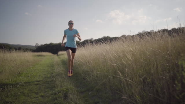 slow motion woman running on path through high dry grass
