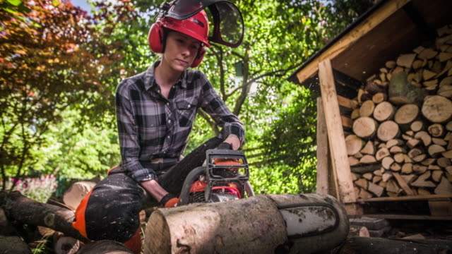 slow motion: woman sawing tree trunk with a chainsaw - firewood stock videos & royalty-free footage