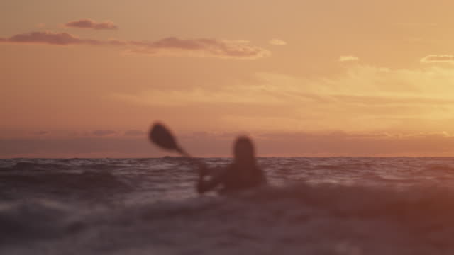Slow motion, woman sea kayaks at sunset