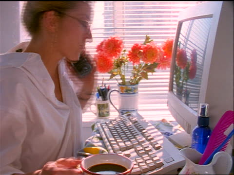 slow motion woman sitting at computer at home while drinking coffee + talking on cordless phone