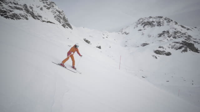 slow motion woman skiing in downhill position
