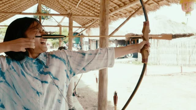 slow motion : woman stretches arrow for the bow and aim at the target - longbow stock videos and b-roll footage