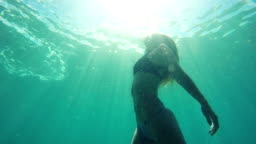 Slow Motion Woman swimming underwater towards surface with beautiful sun flares in slow motion