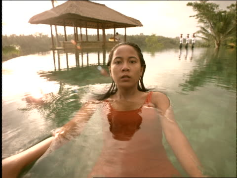 slow motion woman swims backstroke away from camera in pool / women walking in background / bali / indonesia - 室外プール点の映像素材/bロール