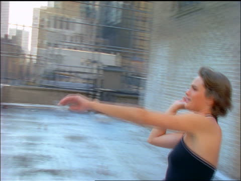 slow motion PAN woman throwing paper airplane off roof of building / NYC
