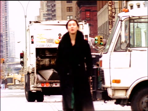 slow motion woman walking on nyc street toward camera / garbage truck in background - garbage truck stock videos and b-roll footage
