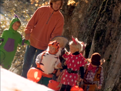 canted slow motion woman walking with group of children in halloween costumes outdoors - 扮装点の映像素材/bロール