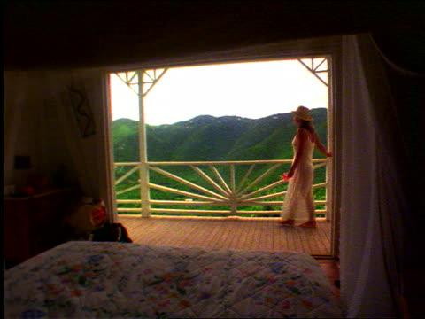 slow motion pan woman wearing dress with hat walking on scenic balcony / st johns, virgin islands - st. john virgin islands stock videos & royalty-free footage