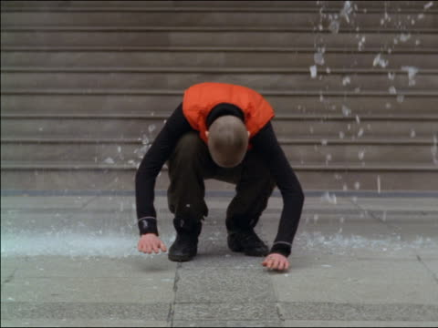slow motion woman with shaved head + pieces of broken glass landing on sidewalk / she stays crouched