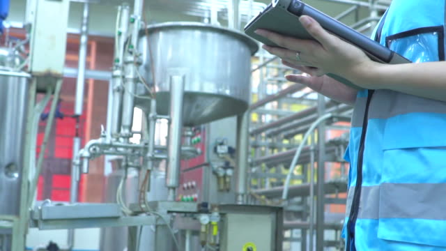slow motion: women engineer working in factory using digital tablet - storage tank stock videos & royalty-free footage