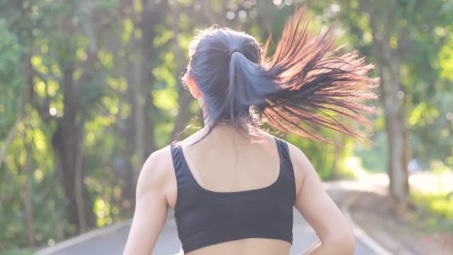 stockvideo's en b-roll-footage met slo mo slow motion vrouwen oefenen hardlopen joggen in het openbare park - jogster
