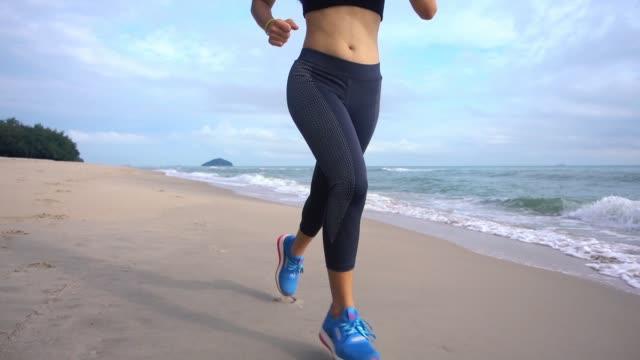 vídeos de stock, filmes e b-roll de fhd lento movimento jovem asiática correndo na praia - sutiã para esportes