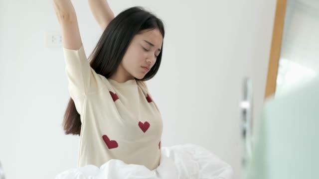 vidéos et rushes de slow motion jeune femme asiatique se réveiller et s'étendant sur le lit dans la chambre à coucher dans le matin - s'étirer