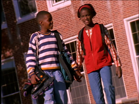 slow motion young black boy + girl holding hands walking toward camera / connecticut - close to stock videos & royalty-free footage