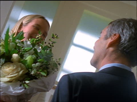 slow motion young blonde woman receiving bouquet of flowers from middle-aged man + kissing on cheeks