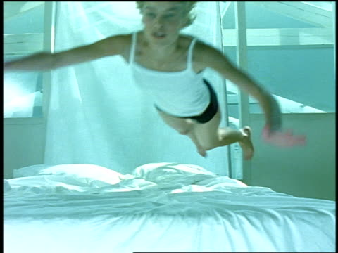 stockvideo's en b-roll-footage met slow motion young blonde woman wearing underwear jumping onto bed + looking at camera - dubbel bed