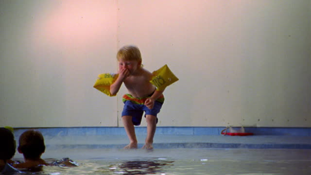 slow motion young boy in swimsuit + water wings holding nose + jumping into indoor pool / others in water