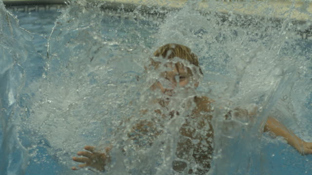 Slow motion young boy jumping into swimming pool backwards, Spain, MS (Individual frames may also be used as a still image. Each frame in its raw state is about 6MB or about 12MB as a 16 bit TIFF)