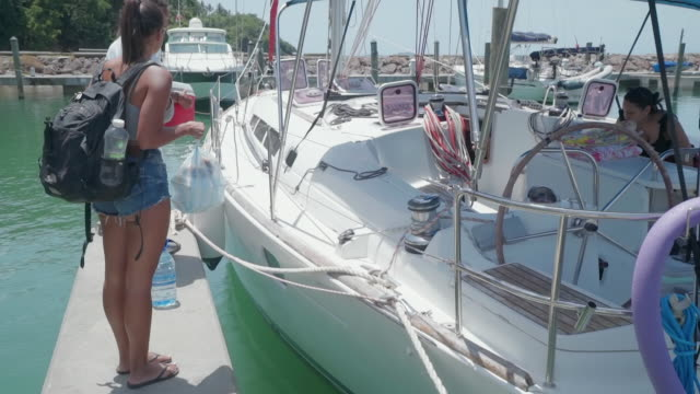 slow motion: young couple on pier joining young couple on yacht in el limon, dominican republic - getting on stock videos & royalty-free footage