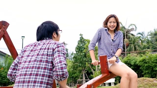 vídeos y material grabado en eventos de stock de cámara lenta : pareja joven en subibaja en el patio de juegos - balancín