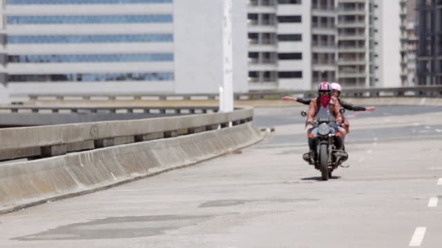 ws slow motion young couple riding motorbike  to camera on city road - fly från verkligheten bildbanksvideor och videomaterial från bakom kulisserna
