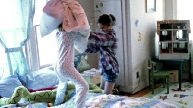 slow motion young girl in pajamas + teenage girl having pillow fight on bed in bedroom - 枕投げ点の映像素材/bロール