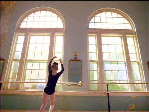 slow motion young girl pirouetting in leotard in dance studio - pirouette stock videos and b-roll footage