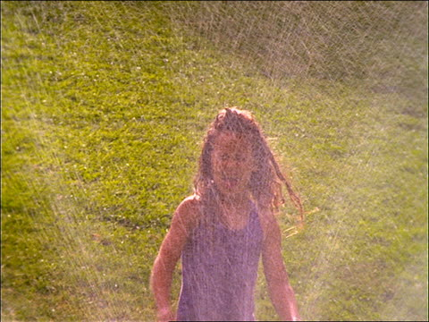 slow motion young girl running thru sprinkler in grass