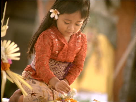 vidéos et rushes de slow motion young hindu girl praying with flowers / incense smoke in foreground / bali / indonesia - cinématographie