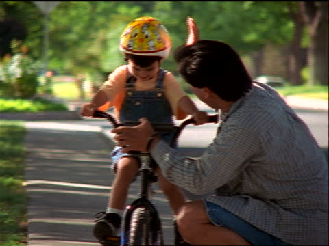 slow motion young Hispanic boy in helmet riding bicycle to man on sidewalk / they high five + hug