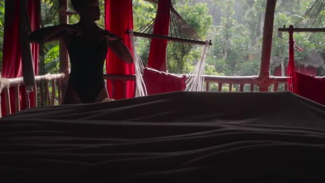 vidéos et rushes de slow motion: young in black bodysuit in open, thatched hut in el limon, dominican republic - linge de lit
