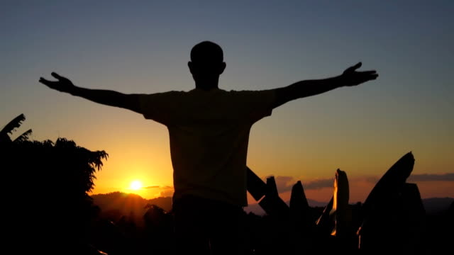 slow motion young man arms at the sunset mountaintop view. - god stock videos & royalty-free footage