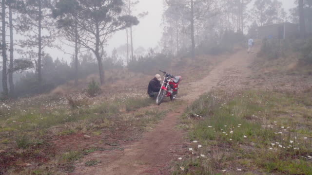 slow motion: young man crouched next to motorcycle in misty landscape - dominican republic stock videos and b-roll footage
