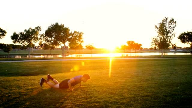 公園で burpees をやってスローモーション若い男 - 胸筋点の映像素材/bロール